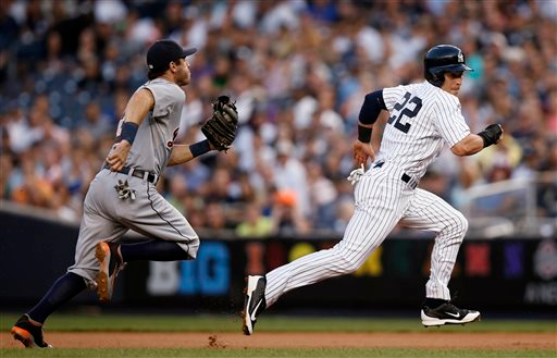 . Detroit Tigers second baseman Ian Kinsler (3) chases New York Yankees Jacoby Ellsbury (22), who races back to first base after being caught off base in the first inning of a baseball game at Yankee Stadium in New York, Tuesday, Aug. 5, 2014. Ellsbury slid safely back and avoided being tagged out. (AP Photo/Kathy Willens)