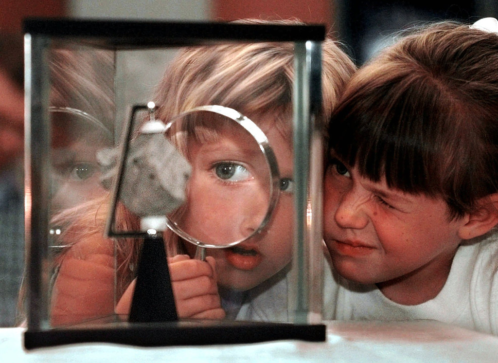 . Six-year-olds Amanda Johanson, left, and Camille Baer share a magnifiying glass while inspecting  a Martian meteorite on display at the New Mexico Museum of Natural History and Science in Albuquerque, N.M., Sunday, July13, 1997. The meteorite is one of only 12 meteorites world-wide that has been identified as originating from Mars. (AP Photo/Eric Draper)