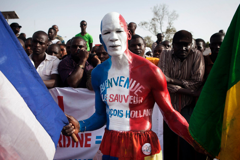 ". A Malian man painted in the colours of the French flag and with the words reading: ""Welcome the savior Francois Hollande\"" poses for a picture before the arrival of France\'s President Francois Hollande at the Independence Plaza in Bamako, Mali February 2, 2013. France will withdraw its troops from Mali once the Sahel state has restored sovereignty over its national territory and a U.N.-backed African military force can take over from the French soldiers, Hollande said on Saturday. REUTERS/Joe Penney"