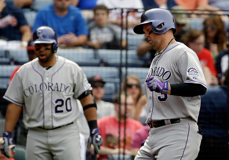 . Colorado Rockies\' Michael Cuddyer, right, crosses home plate after hitting a home run in the second inning of a baseball game against the Atlanta Braves, Saturday, May 24, 2014, in Atlanta. (AP Photo/David Goldman)