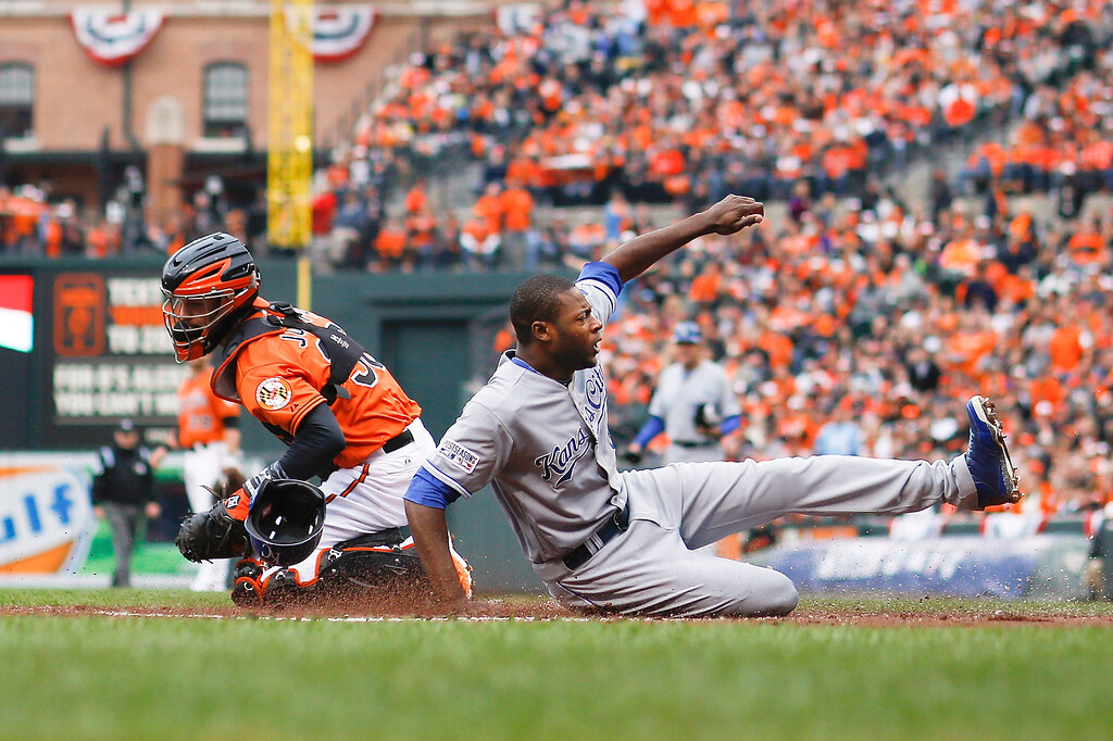 . Kansas City Royals\' Lorenzo Cain scores on a hit by by Eric Hosmer during the first inning of Game 2 of the American League baseball championship series against the Baltimore Orioles Saturday, Oct. 11, 2014, in Baltimore. (AP Photo/Matt Slocum)