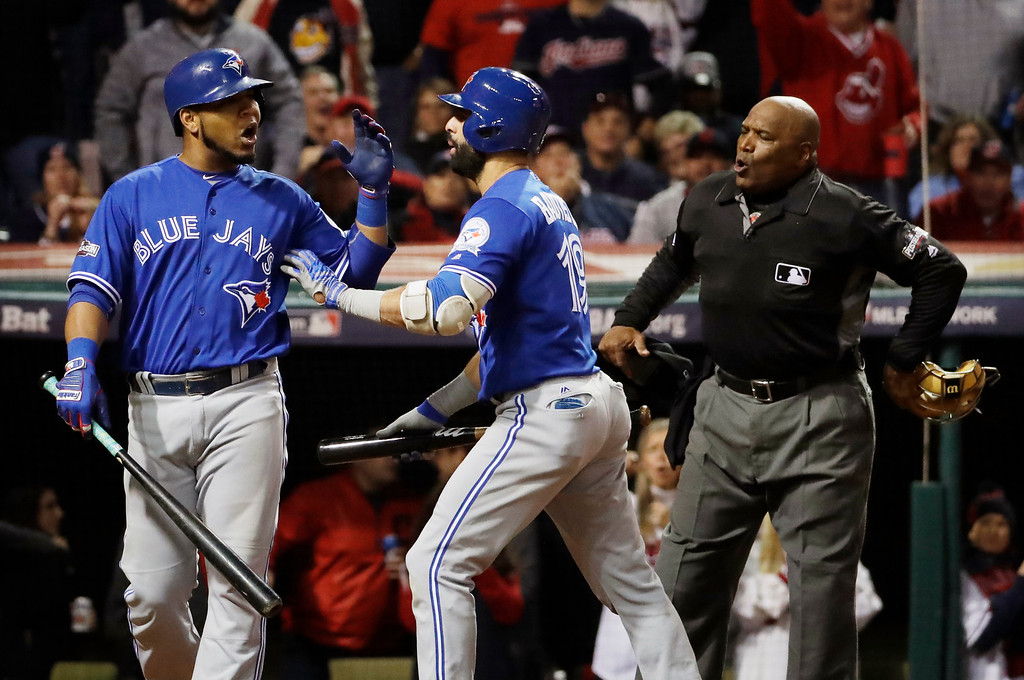 . Toronto Blue Jays\' Jose Bautista, center, pushes Edwin Encarnacion away from home plate umpire Laz Diaz after Encarnacion was called out on strikes during the eighth inning in Game 1 of baseball\'s American League Championship Series against the Cleveland Indians in Cleveland, Friday, Oct. 14, 2016. (AP Photo/Matt Slocum)