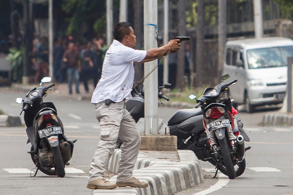 . A plainclothes police officer aims his gun at attackers during a gun battle following explosions in Jakarta, Indonesia Thursday, Jan. 14, 2016. Attackers set off explosions at a Starbucks cafe in a bustling shopping area in Indonesia\'s capital and waged gunbattles with police Thursday, leaving bodies in the streets as office workers watched in terror from high-rise buildings. (AP Photo)