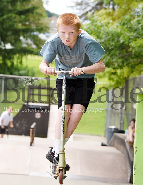 Harold Aughton/Butler Eagle: Noah Scott, 10, of Fenelton goes airborn with his scooter over the jump at Father Marinaro Park Monday afternoon as part of the Grace Youth and Family Foundation summer outreach program. The program runs from 12 - 3:00 p.m.