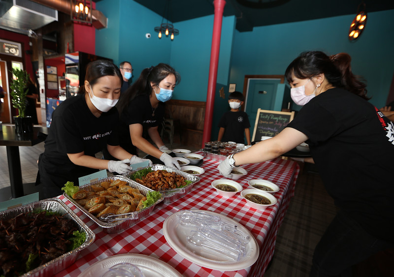Opening of Tasty Dumplings, new restaurant on Market Street at Cardinal O'Connell Parkway. Tasty Dumplings owner Michelle Wang of Billerica, right, and friends who were helping, Meili Jin, left, and Grace Xiao, set out food. (SUN/Julia Malakie)