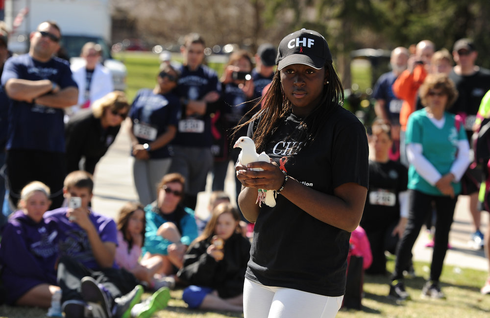 . Amyre Hollis, the 14 year old daughter of Celena, gets ready to release 1 of the 22 doves during the gathering after the race.  Family, colleagues, and friends of slain Denver Police Officer Celena Hollis turned out April 7, 2013 for a 5k run and walk to raise money for a scholarship fun and a memorial bench in City Park in Denver, CO.  Over 300 runners and walkers participated in the race that started at 9:00 am.  The race looped around City Park.  After the race, a gathering was held to remember Hollis and 22 white doves were released in her memory.  (Photo By Helen H. Richardson/ The Denver Post)