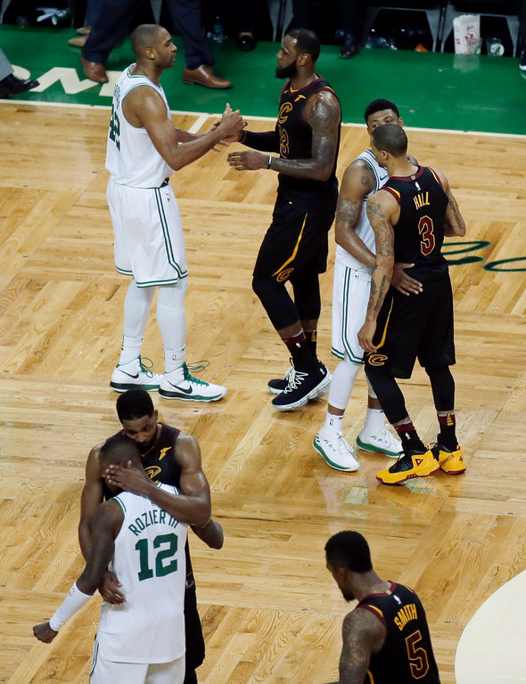 . Boston Celtics forward Al Horford, left, rear, shakes hands with Cleveland Cavaliers forward LeBron James, Celtics guard Marcus Smart, right, speaks to Cavaliers guard George Hill (3), and Cavaliers forward Jeff Green, lower left, embraces Celtics guard Terry Rozier (12) after the Cavaliers beat the Celtics 87-79 in Game 7 of the NBA basketball Eastern Conference finals, Sunday, May 27, 2018, in Boston. (AP Photo/Charles Krupa)