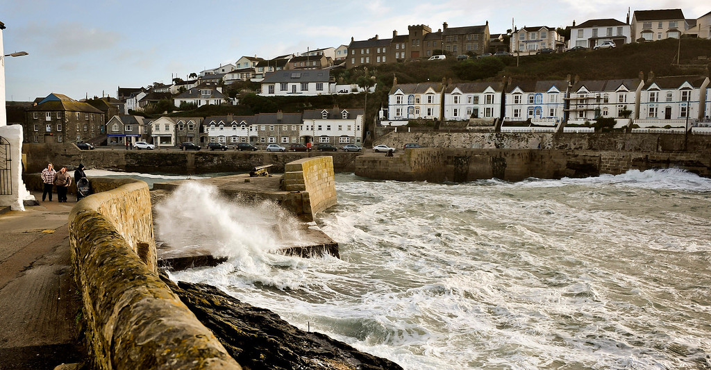 . People walk along a path as waves crash onto a seawall protecting the harbor of Porthleven, Cornwall, southwest England, Sunday, Oct. 27, 2013. Forecasters say a severe storm will hit the southern half of Britain later Sunday, bringing heavy rains and gusts of 60 to 80 miles per hour (100 to 130 kilometers per hour, with the potential to cause widespread and severe disruption from falling trees, power cuts and flooding. (AP Photo/PA, Ben Birchall)