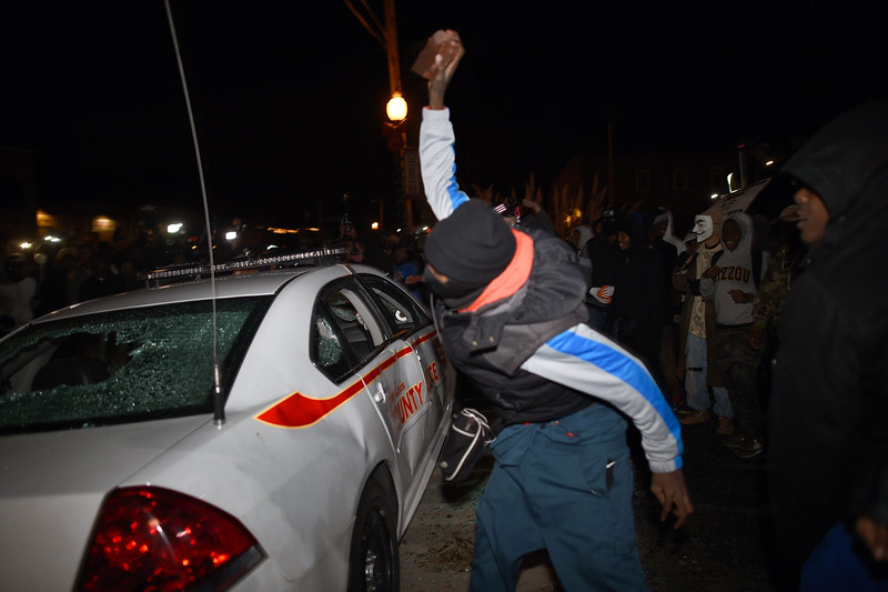 . A demonstrator attacks a police car  after learning that the police officer who shot dead 18-year-old Michael Brown will not face charges, outside the police station in Ferguson, Missouri, on November 24, 2014. US President Barack Obama urged calm on November 24 as violent protests broke out on the streets of Ferguson after a grand jury decided a white policeman will not face charges for killing a black teen. JEWEL SAMAD/AFP/Getty Images