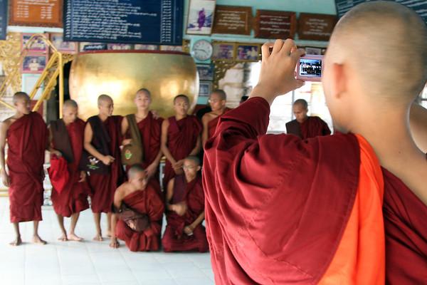 Monks pose for a souvenir photo at Manuha Stupa, Bagan, Myanmar