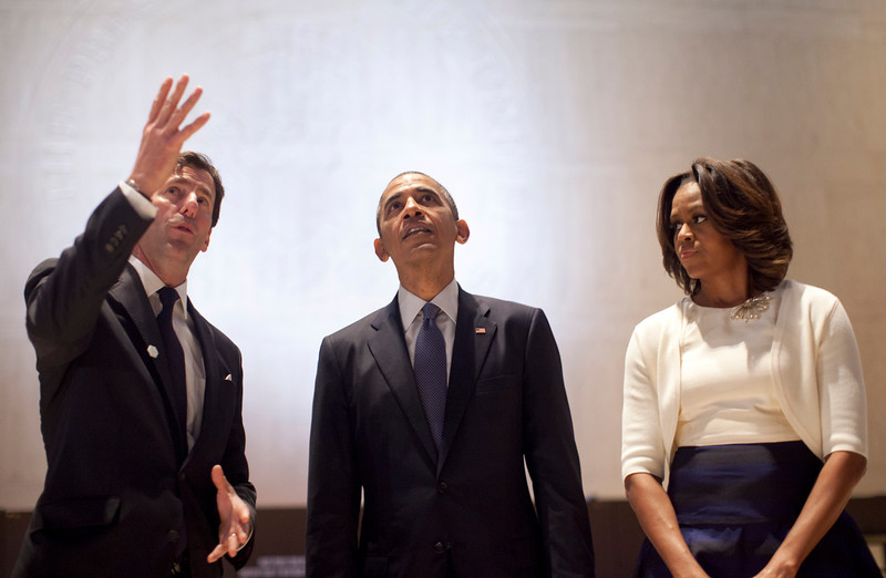 . LBJ Presidential Library Director Mark Updegrove, left, speaks to President Barack Obama and first lady Michelle Obama as they tour the Great Hall at the LBJ Presidential Library, Thursday, April 10, 2014, in Austin, Texas, as they attend a Civil Rights Summit to commemorate the 50th anniversary of the signing of the Civil Rights Act. (AP Photo/Carolyn Kaster)