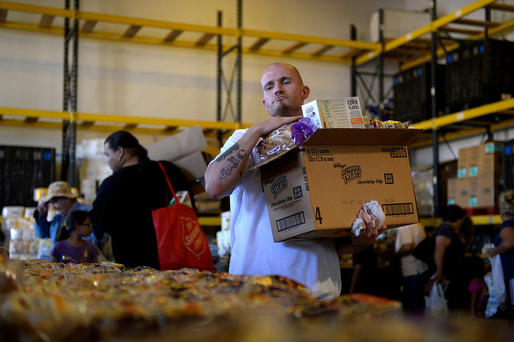 . Parolee Thomas Vescio fills his box with what he can at a food bank in Commerce City on July 11, 2013 in Commerce City, Colorado. He has to pass on many items because he has nothing to cook with and nowhere to keep anything cold.  (Photo By Joe Amon/The Denver Post)
