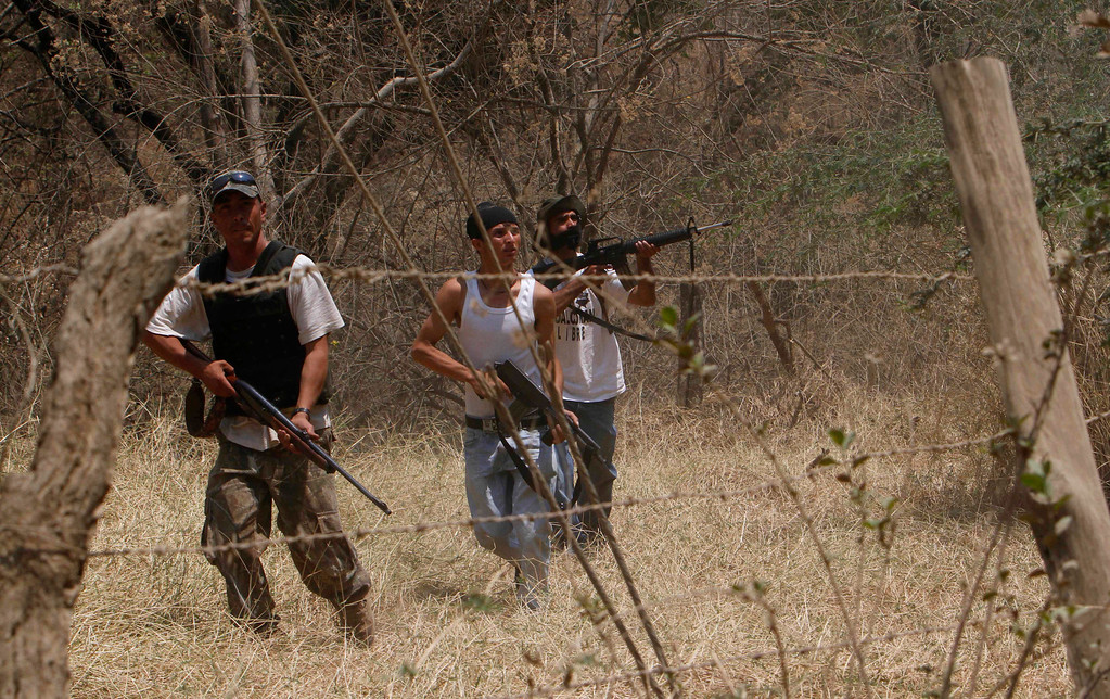 . In this May 20, 2013 photo, men belonging to a local self-defense group enter a ranch to recover cattle allegedly stolen by the Knights Templar drug cartel near the town of Cualcoman, Mexico. Self-defense groups started to spring up in February to fight back the Knights Templar drug cartel which is extorting protection payments from cattlemen and lime growers, butchers and even marijuana growers. The federal government sees both the self-defense forces and the cartel as dangerous enemies. (AP Photo/Marco Ugarte)
