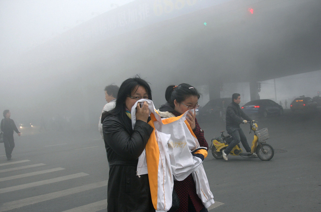 . Two women cover up their mouths and noses with a jacket as they cross a street covered by dense smog in Harbin, northern China, Monday, Oct. 21, 2013. Visibility shrank to less than half a football field and small-particle pollution soared to a record 40 times higher than an international safety standard in one northern Chinese city as the region entered its high-smog season. (AP Photo/Kyodo News) J