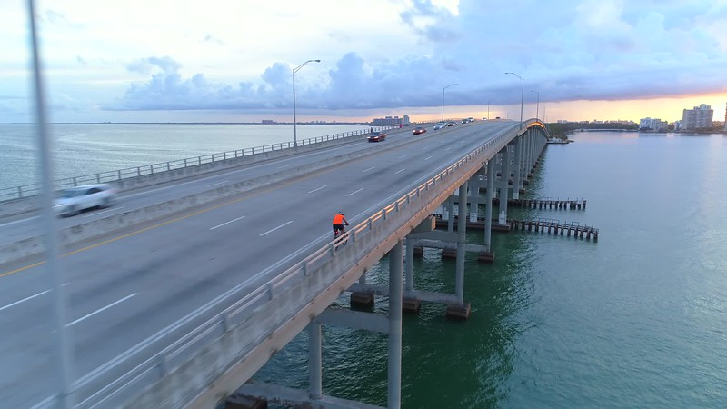 Aerial footage of a cyclist riding up a bridge Miami Rickenbacker Causeway
