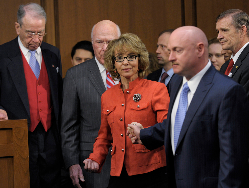 Description of . Former Arizona Rep. Gabrielle Giffords, center, who was seriously injured in the mass shooting that killed six people in Tucson, Ariz. two years ago, arrives on Capitol Hill in Washington, Wednesday, Jan. 30, 2013, to speak before the Senate Judiciary Committee hearing on gun violence. From left are, the committee's ranking Republican, Sen. Charles Grassley, R-Iowa, Committee Chairman Sen. Patrick Leahy, D-Vt., Giffords, and her husband Mark Kelly . (AP Photo/Susan Walsh)