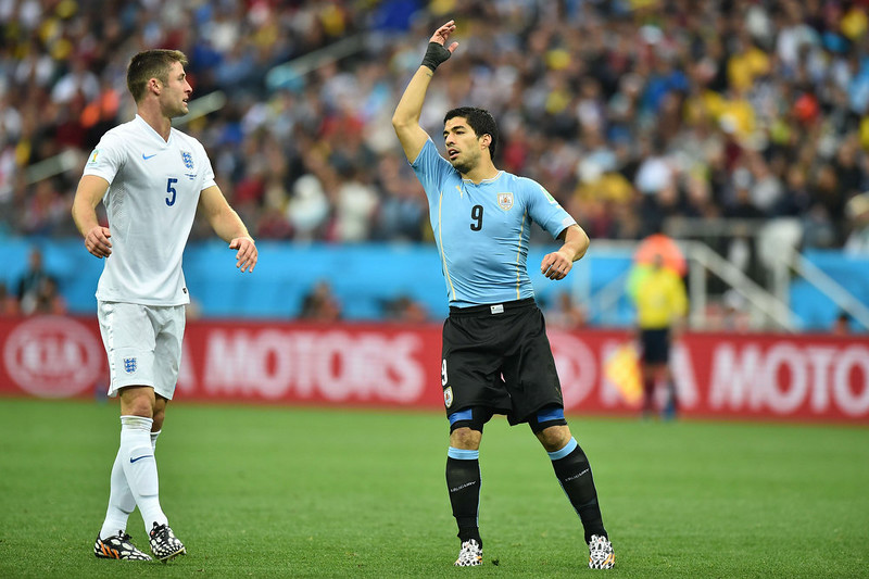 . Uruguay\'s forward Luis Suarez (R) protests after a free-kick was awarded as England\'s defender Gary Cahill looks on during the Group D football match between Uruguay and England at the Corinthians Arena in Sao Paulo on June 19, 2014, during the 2014 FIFA World Cup. BEN STANSALL/AFP/Getty Images