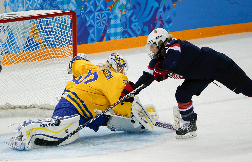 . Goalkeeper Kim Martin Hasson of Sweden blocks a penalty shot by Jocelyne Lamoureux of the United States during the third period of the 2014 Winter Olympics women\'s semifinal ice hockey game at Shayba Arena, Monday, Feb. 17, 2014, in Sochi, Russia. (AP Photo/Julio Cortez)