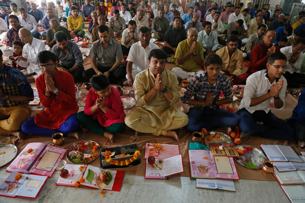 . Indian businessmen perform rituals during Chopada Pujan, or a mass prayer ceremony dedicated to the worship of the account book, on the occasion of Diwali, the Hindu festival of lights, in Ahmadabad, India, Thursday, Oct. 19, 2017. During Chopada Pujan ledgers and new account books are opened by the mercantile community following a special prayer and worship before the idols of Lord Ganesha and Hindu Goddess of wealth Lakshmi to earn their blessings. (AP Photo/Ajit Solanki)