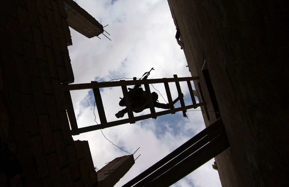. A Free Syrian Army fighter carries his weapon as he uses a ladder to climb into a building in Deir al-Zor on April 20, 2013. Picture taken April 20, 2013.  REUTERS/Khalil Ashawi