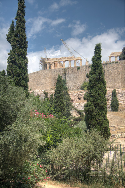 The Parthenon and the Acropolis peek through trees and buldings around Athens. (HDR)