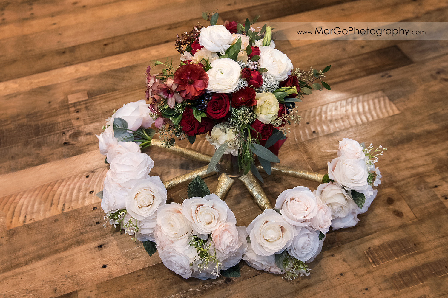 white and red flower wedding bouquets on wooden floor at Sunol's Casa Bella