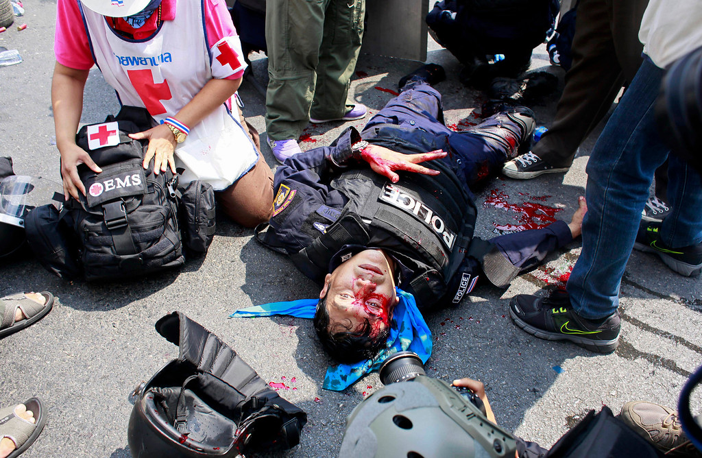 . A riot police officer lies motionless after a massive head injury during a clash with protesters in Bangkok, Thailand, Tuesday, Feb. 18, 2014. Hundreds of riot police attempted to clear out anti-government protest sites around Thailand\'s capital on Tuesday, triggering clashes that left three people dead and 57 others injured. (AP Photo/Wally Santana)