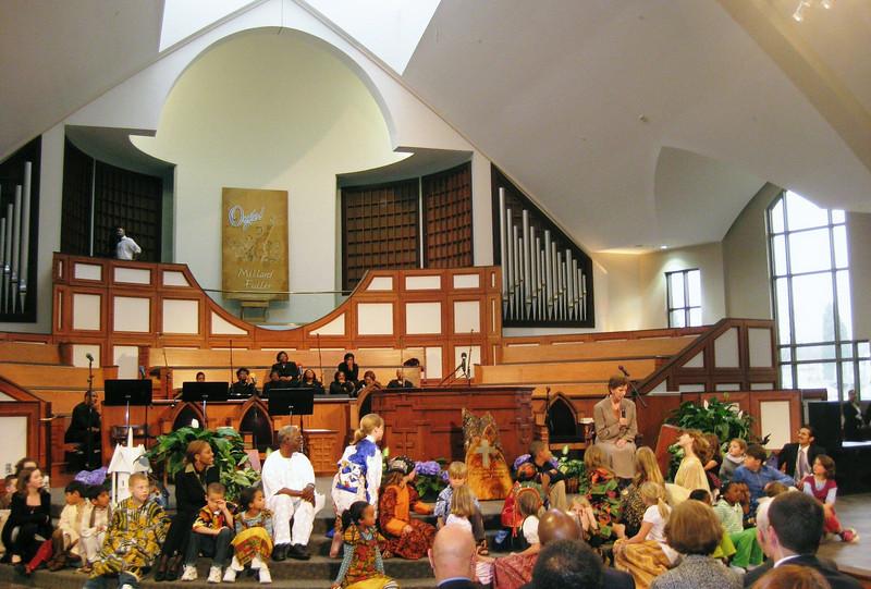 Linda Fuller telling story to children in traditional international dress. jg