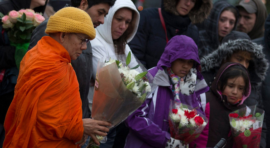 . A Buddhist monk from Thailand leaves flowers for victims of the Sandy Hook Elementary shooting at a memorial in Sandy Hook Village in Newtown, Connecticut December 16, 2012. Worshippers filled Sunday services to mourn the victims of a gunman\'s elementary school rampage that killed 20 children and six adults with President Barack Obama due to appear later at an interfaith vigil to help this shattered Connecticut town recover.   REUTERS/Adrees Latif