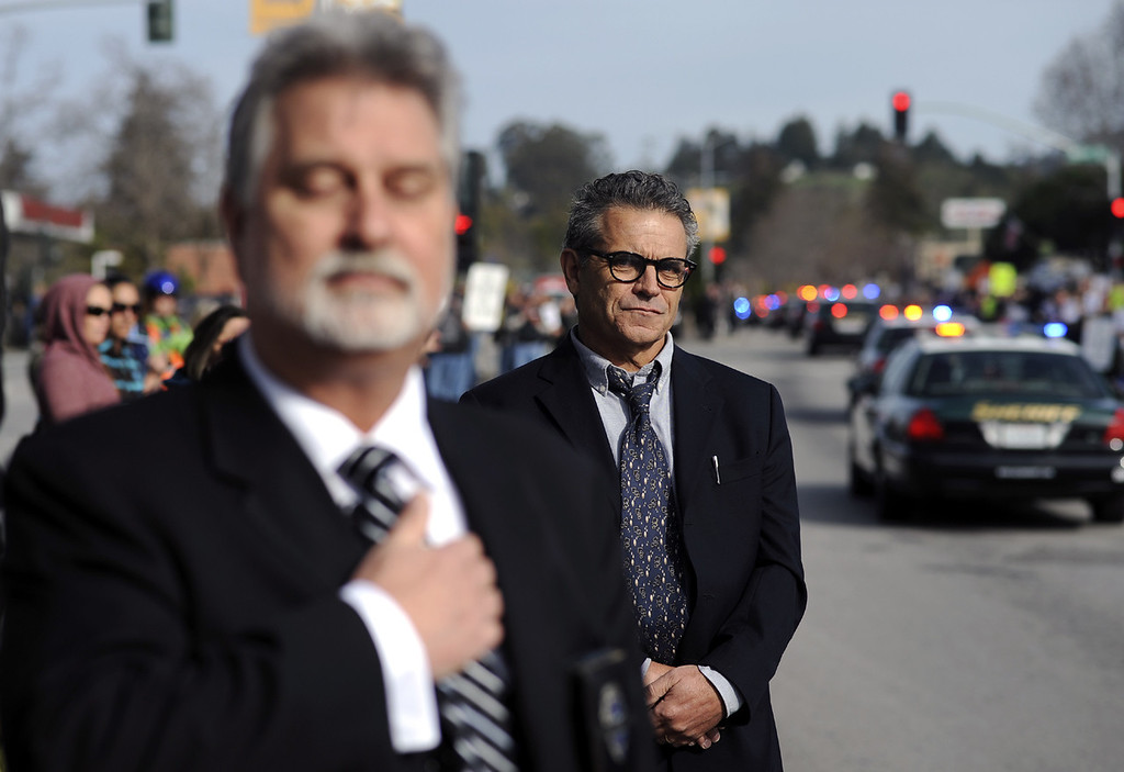 . Retired Lieutenant Ken Knuth, left, stands in salute as the procession for detectives Sgt. Loran \'Butch\' Baker and Elizabeth Butler moves down Ocean Street in Santa Cruz Thursday morning en route to HP Pavilion in San Jose for the officers\' memorial services. (Matthew Hintz/Sentinel)