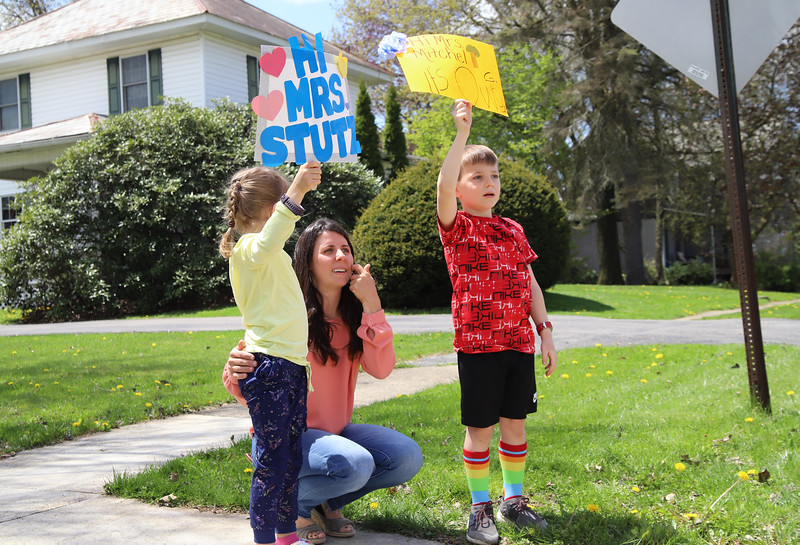 Owen Green (right) and his sister Harper hold up signs and wave to teachers with their mother Jo Green Thursday during Moraine Elementary's teacher parade. Seb Foltz/Butler Eagle
