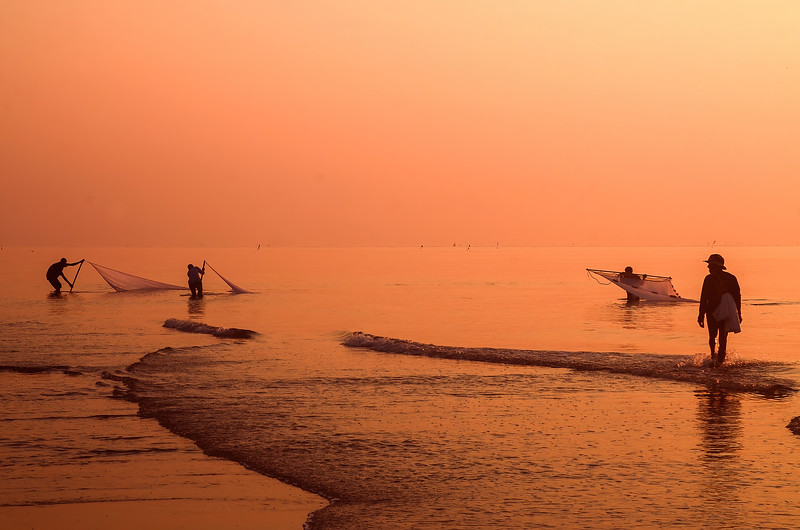 Colourful pink glow tropical sunrise seascape with wading fishermen in silhouette