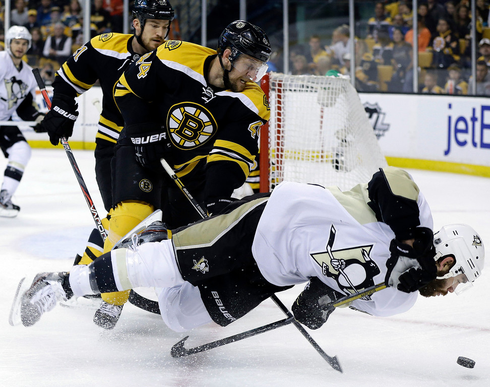 . Boston Bruins defenseman Dennis Seidenberg (44) checks Pittsburgh Penguins right wing Pascal Dupuis to the ice during the first period of Game 4 in the Eastern Conference finals of the NHL hockey Stanley Cup playoffs, in Boston on Friday, June 7, 2013. (AP Photo/Elise Amendola)