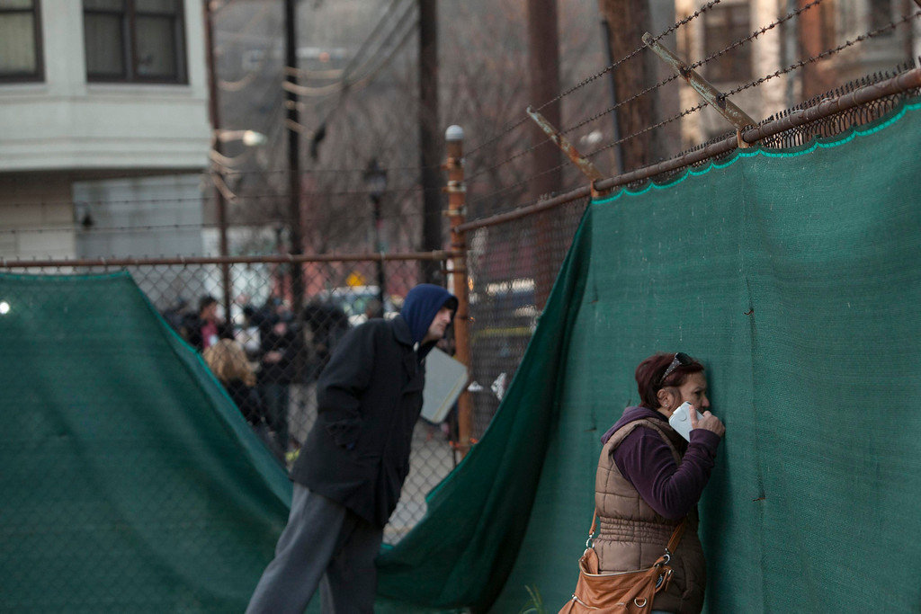 . Residents peer through a fence to see where police cordoned off a crime scene related to the shootings at Sandy Hook Elementary School, in Hoboken, New Jersey, December 14, 2012. In Hoboken, New Jersey, police cordoned off a block in connection with the Connecticut shootings but an officer told reporters there was no body inside, contrary to an earlier media report. REUTERS/Andrew Kelly
