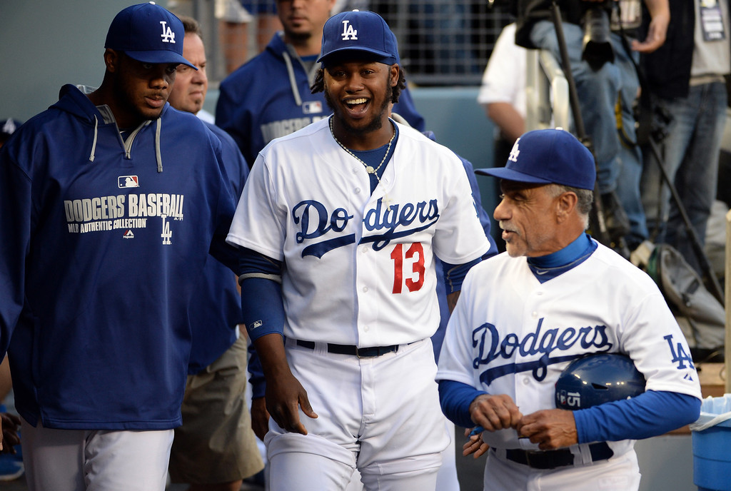 . Los Angeles Dodgers\' Hanley Ramirez (13) smiles in the dugout with relief pitcher Kenley Jansen, left, and first base coach Davey Lopes, right, prior to a baseball game against the Philadelphia Phillies on Tuesday, April 22, 2013 in Los Angeles.   (Keith Birmingham/Pasadena Star-News)