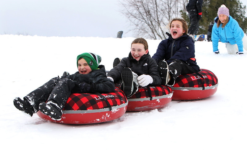 Sledding hill at Cherry Hill Ice Cream in Lunenburg is busy after a Nor'easter brings fresh snow.  From left on tubes, Danny Harrington, 10, Ava Kelly, 11 and Danny's sister Leah Harrington, 11, all of Lunenburg. (SUN/Julia Malakie)