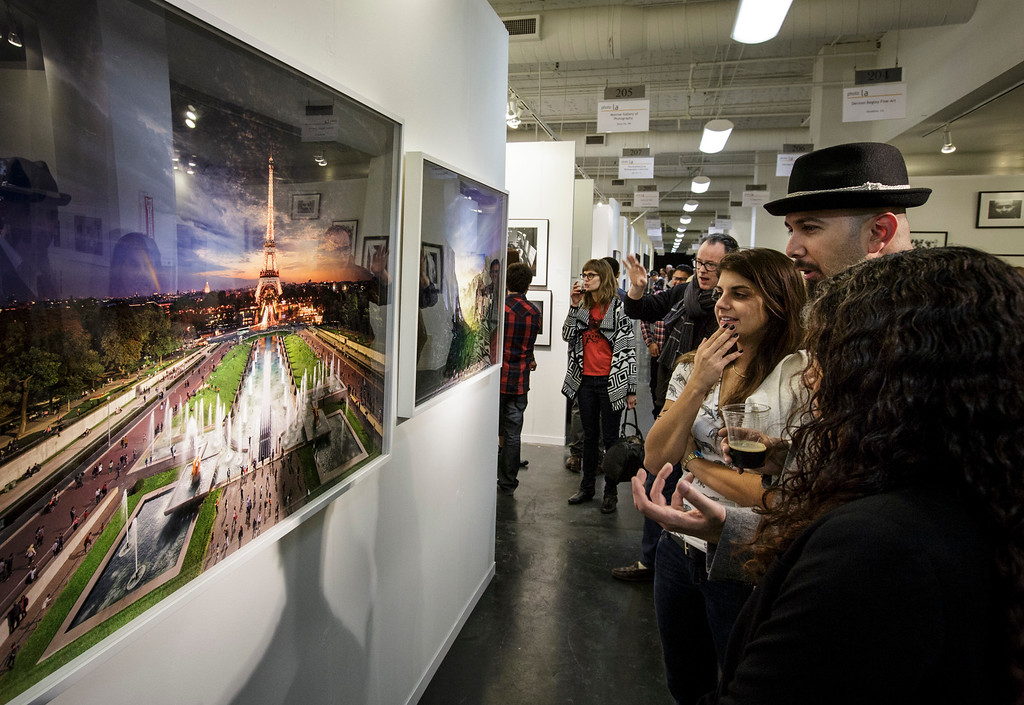 ". Visitors view Stephen Wilkes\' photo ""Eiffel Tower, Paris, Day into night, 2013\""  at the photo la opening party held at The REEF/LA Mart in Los Angeles, CA. January 15, 2015.  Photo by David Sprague/Special to the Daily News"