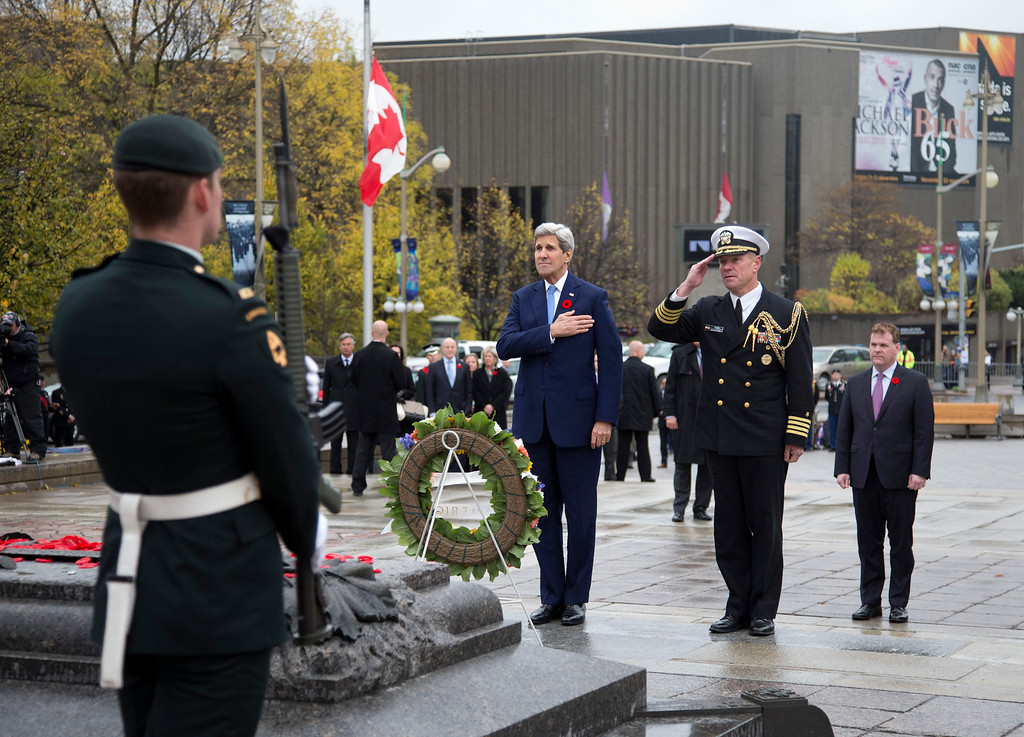 . From left, Secretary of State John Kerry, and U.S. Naval Attache, Capt. Charles J. Cassidy, stand after placing a wreath at the Tomb of the Unknown Soldier, as Canadian Foreign Minister John Baird, right, watches during a ceremony at the National War Memorial in Ottawa, Canada, Tuesday, Oct. 28, 2014. Canadians are mourning the loss of Cpl. Nathan Cirillo, the army reservist who was shot dead as he stood guard before the Tomb of the Unknown Soldier.(AP Photo/Carolyn Kaster, Pool)