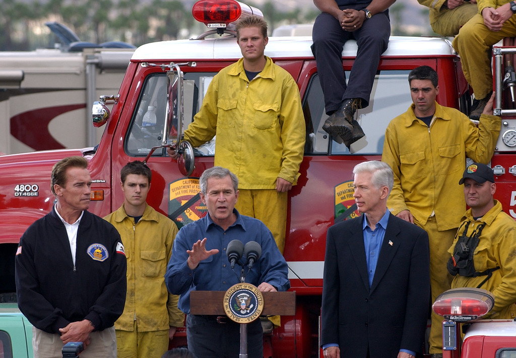 . President  Bush, flanked by California Gov, Gray Davis, right,  and California Governor-elect Arnold Schwarzenegger, speaks to a crowd of firefighters and volunteers at the Gillespie Field base camp in El Cajon, Calif. Tuesday Nov. 4, 2003. (AP PHoto/Eric Gay)