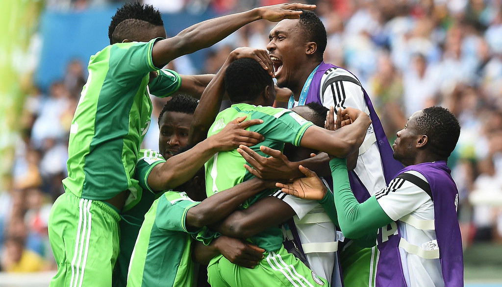 . Nigeria\'s forward Ahmed Musa is mobbed by teammates as he celebrates scoring during the Group F football match between Nigeria and Argentina at the Beira-Rio Stadium in Porto Alegre on June 25, 2014,during the 2014 FIFA World Cup. JEWEL SAMAD/AFP/Getty Images
