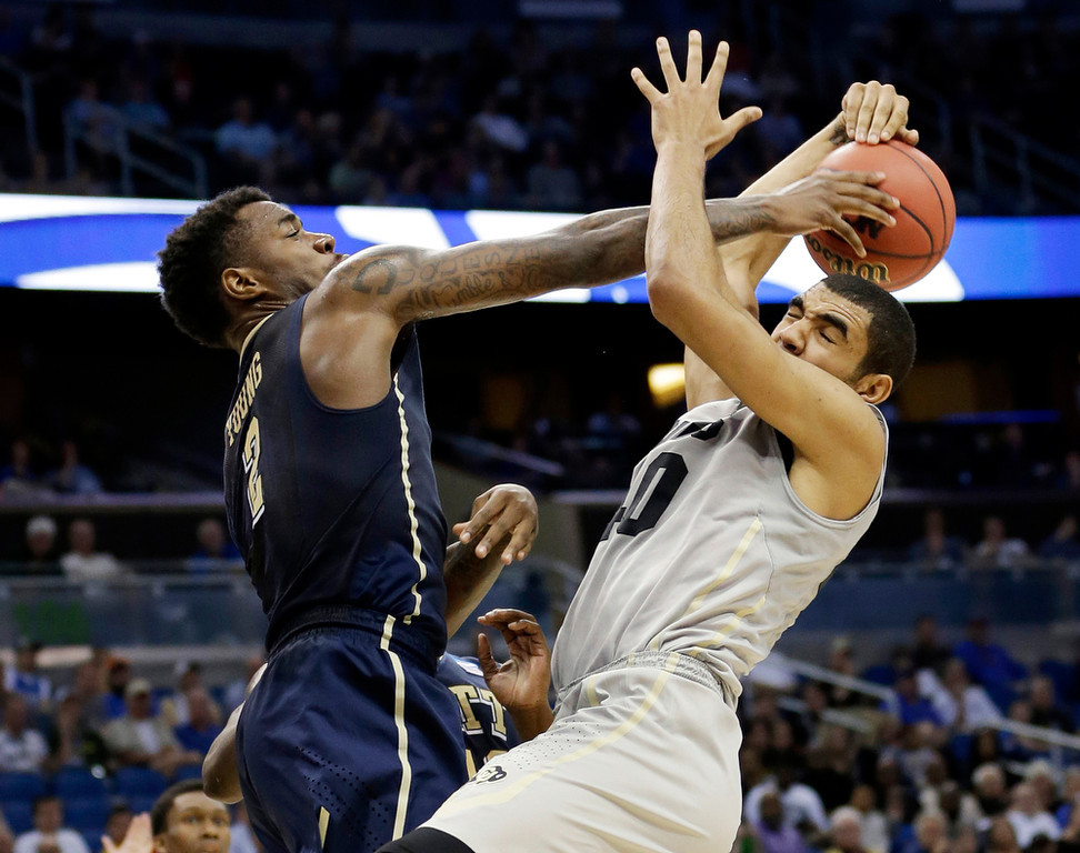 . Pittsburgh forward Michael Young (2) blocks a shot to the basket by Colorado forward Josh Scott during the first half in a second-round game in the NCAA college basketball tournament Thursday, March 20, 2014, in Orlando, Fla. (AP Photo/John Raoux)