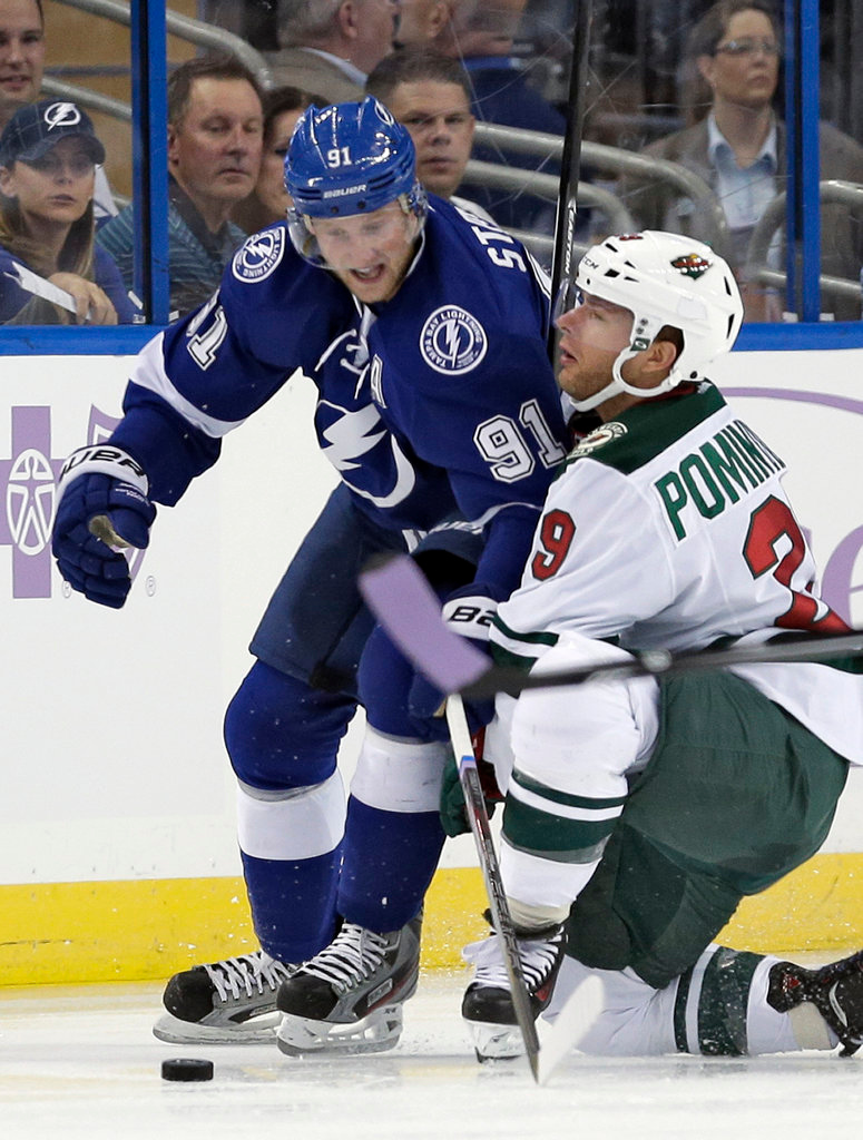 . Tampa Bay Lightning center Steven Stamkos (91) and Minnesota Wild right wing Jason Pominville (29) tangle while chasing a loose puck during the first period. (AP Photo/Chris O\'Meara)
