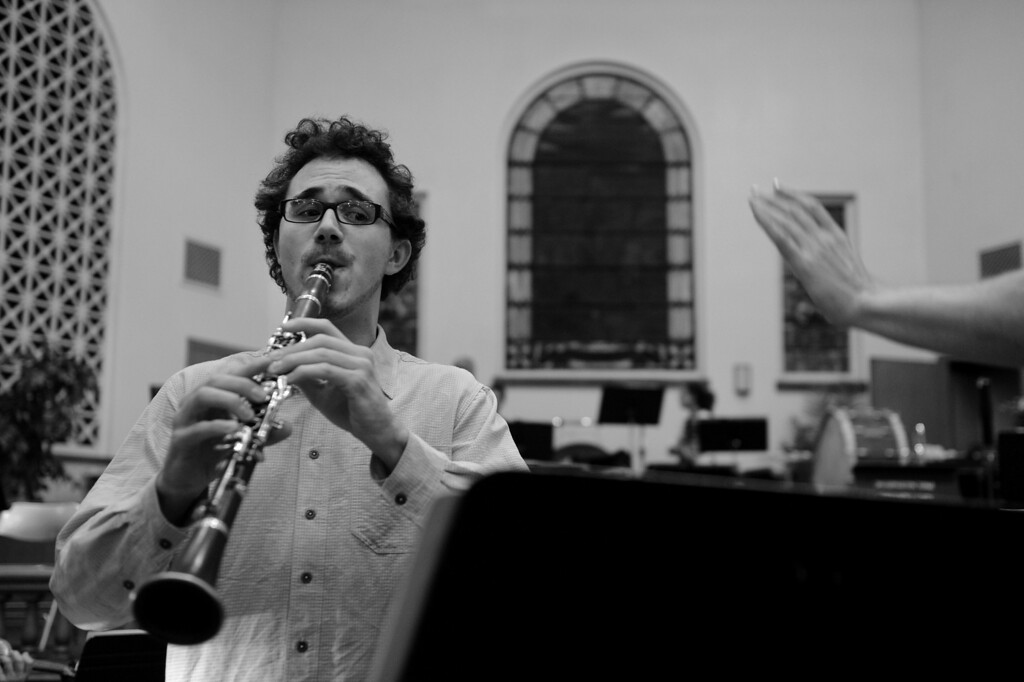""". Shaun Burley works on his clarinet solo during the Denver Philharmonic Orchestra rehearsal at the KPOF Concert Hall in Denver, CO, Monday October 01, 2012.  Burley, 27, said he\'s been playing since the 3rd grade but his love of music started earlier, \""""I remember one day in music class. It was 1st or 2nd grade, our music teacher played a piece by Edvard Grieg, the �Peer Gynt� suite and in particular, �In the Hall of the Mountain King�... The story was so vivid in my head, I could see precisely what was going on. I made a connection between storytelling and music. That was like a eureka moment for me...\""""  Burley said his solo performance of Aaron Copeland\'s Clarinet Concerto at a recent concert went well, \""""I couldn\'t tell you much about it because I was so nervous. I was nervous... throughout. I was nervous going into it, I was nervous during it and I was nervous afterwards... It went well. I wouldn\'t take it back or do it over - but I\'d love to do it again. I spent so much time preparing and I had 20 minutes to display all that work.\"""" Craig F. Walker, The Denver Post"""