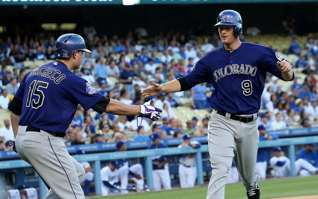 . LOS ANGELES, CA - JULY 12:  DJ LeMahieu #9 of the Colorado Rockies is greeted by Jordan Pacheco #15 after he scores a run in the first inning against the Los Angeles Dodgers at Dodger Stadium on July 12, 2013 in Los Angeles, California.  (Photo by Stephen Dunn/Getty Images)