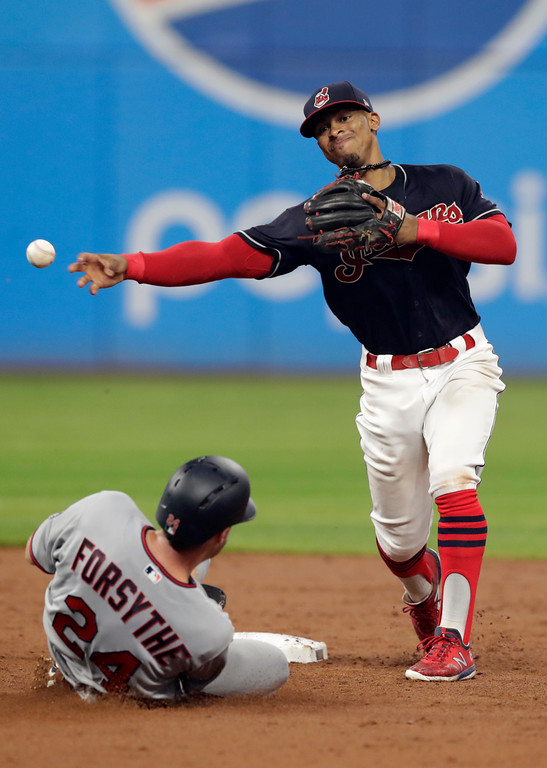 . Cleveland Indians\' Francisco Lindor, right, throws to first base after getting Minnesota Twins\' Logan Forsythe out at second base in the sixth inning of a baseball game, Tuesday, Aug. 7, 2018, in Cleveland. Jake Cave was out at first base for the double play (AP Photo/Tony Dejak)