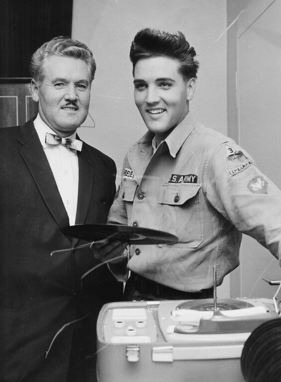 . Presley at his German off-base home - Singer Elvis Presley joins his father at the record player in his off-base home here today. Presley, who drives a Jeep for the Army, hopes to be back to his entertaining job before next spring. (11/10/1959)(AP Photo)