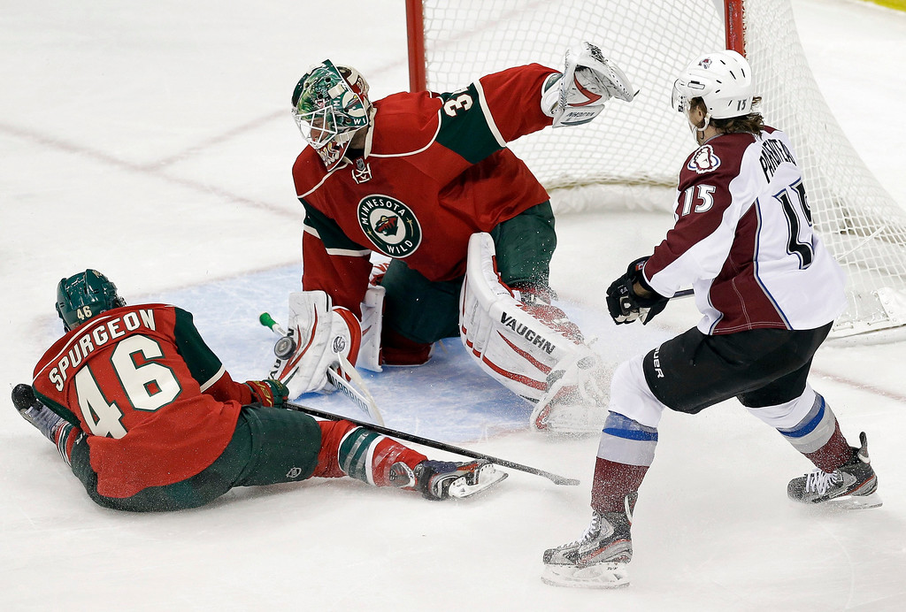 . Minnesota Wild\'s Jared Spurgeon, left, comes to the aid of goalie Niklas Backstrom, of Finland, to stop a shot on goal as Colorado Avalanche\'s P.A. Parenteau, right, looks for a scoring opportunity in the first period of an NHL hockey game on Thursday, Feb. 14, 2013 in St. Paul, Minn. (AP Photo/Jim Mone)