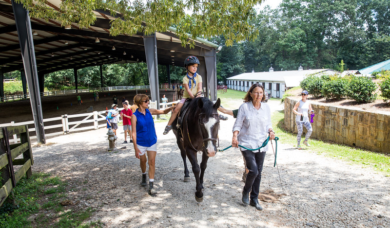 Working to strengthen muscles and work toward physical therapy goals, 5-year-old Brooke Campbell starts her session at Chastain Horse Park.  The multiple therapeutic programs at the center are for special needs campers and for those in need of physical and occupational therapies.  The program is comprised of professional therapist, equestrians and volunteers.    (Jenni Girtman / Atlanta Event Photography)