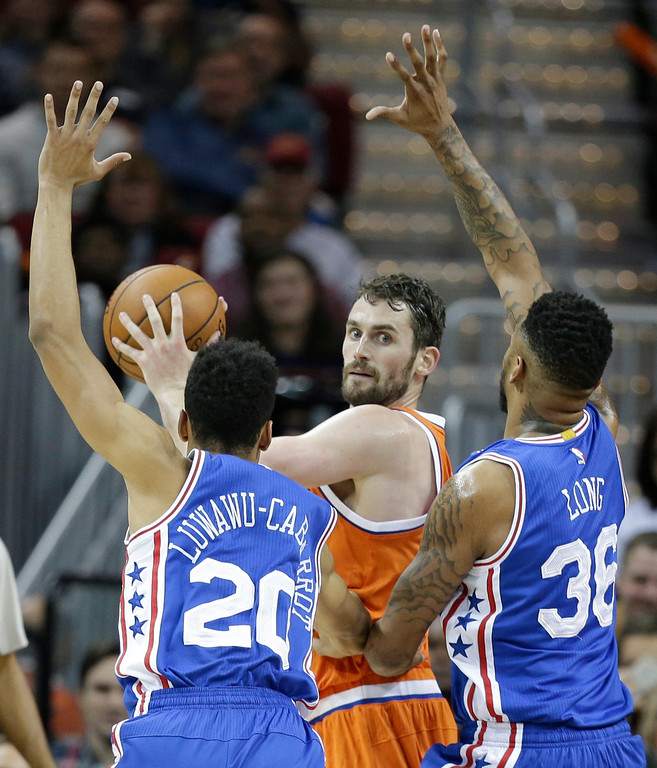 . Cleveland Cavaliers\' Kevin Love (0) loos to pass against Philadelphia 76ers\' Timothe Luwawu-Cabarrot (20), from France, and Shawn Long (36) in the second half of an NBA basketball game, Friday, March 31, 2017, in Cleveland. The Cavaliers won 122-105. (AP Photo/Tony Dejak)