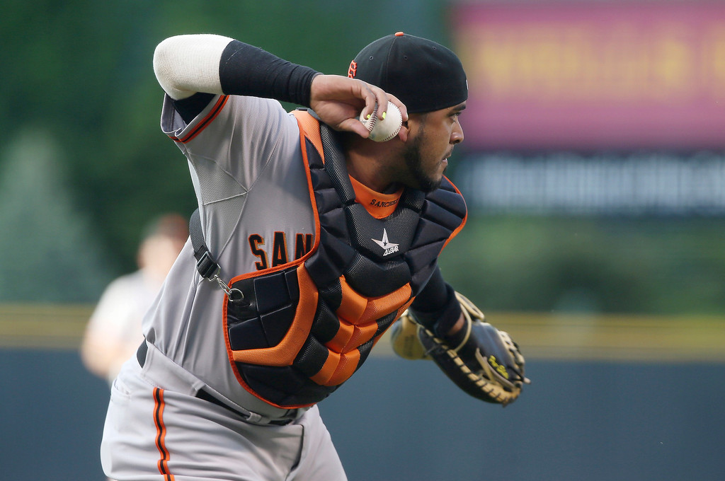 . San Francisco Giants catcher Hector Sanchez throws to first base to put out Colorado Rockies\' Troy Tulowitzki after he hit a weak gorund ball in front of the plate in the first inning of a baseball game in Denver on Tuesday, May 20, 2014. (AP Photo/David Zalubowski)